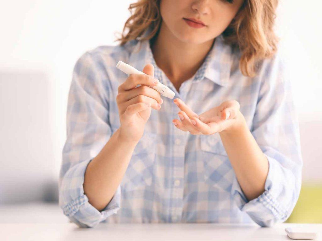 woman using lancet to prick finger