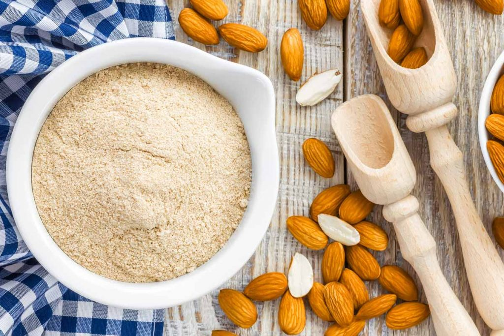 almond flour with almonds and wood scoops