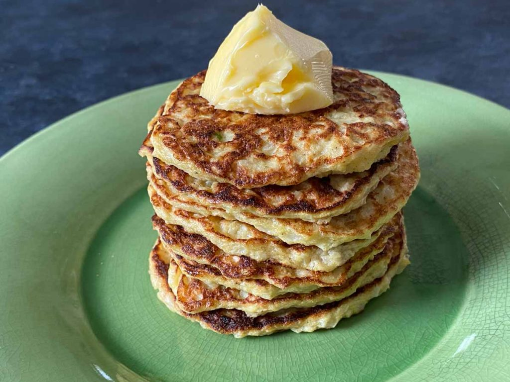 stack of cauliflower patties with butter on plate