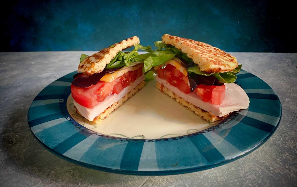 chaffle sandwich cut in half on plate