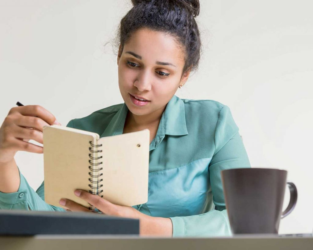 young woman thinking with notebook and coffee cup