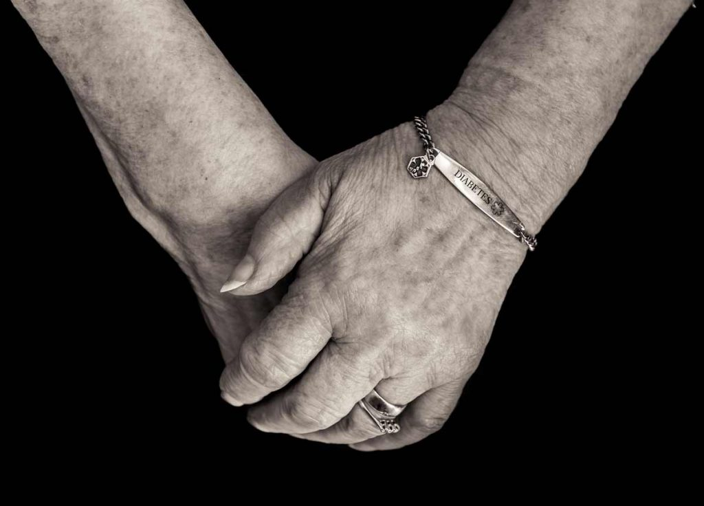 Older woman hands crossed with diabetes bracelet
