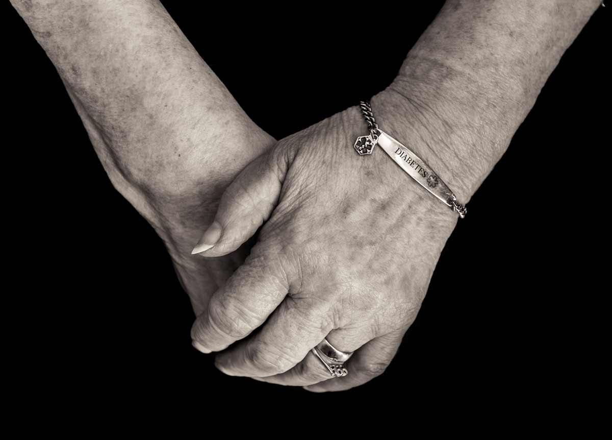 Older woman hands crossed with diabetes bracelet